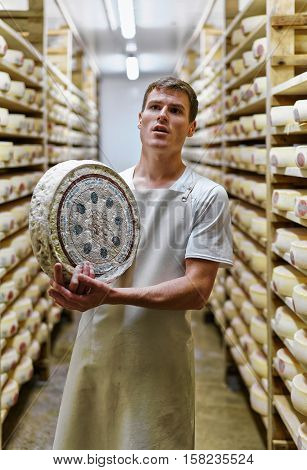 Cheesemaker Holding Wheel Of Comte Cheese At Franche Comte Creamery