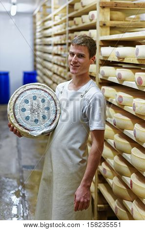 Cheesemaker Holds Wheel Of Comte Cheese At Creamery
