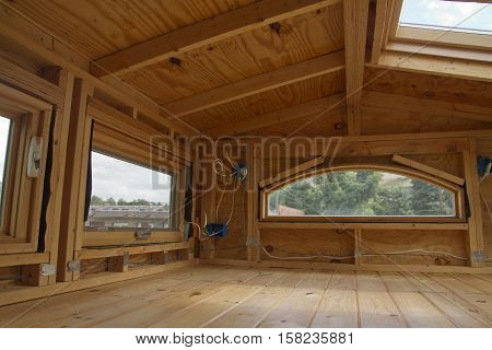 A beautiful tiny house loft in the process of being built made of wood with windows a skylight and exposed electrical wiring