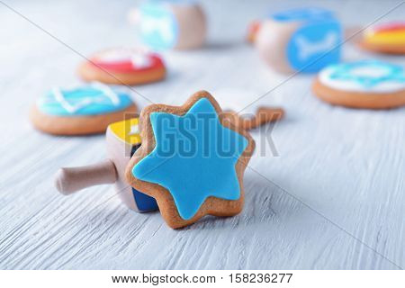 Tasty glazed cookie and dreidel for Hanukkah on light wooden table, closeup