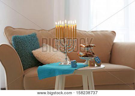 Menorah, dreidels and cookies for Hanukkah on stool in living room