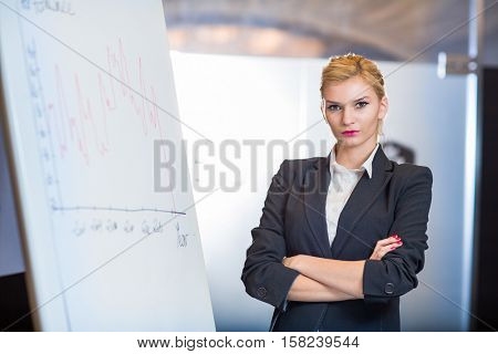Woman making a business presentation - business success growth chart. Business woman drawing graph showing profit growth on whiteboard