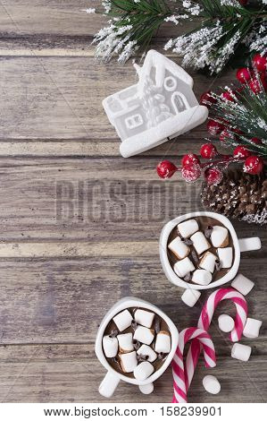 Christmas still life - two cups of hot chocolate with marshmallow candies toy house and branch of fir with berries. Copy space