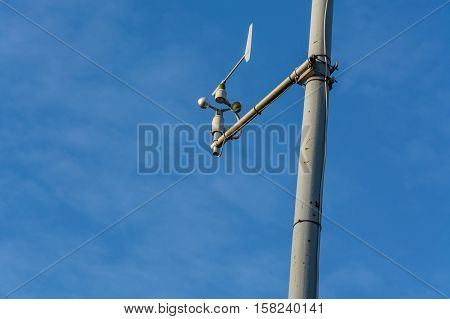Weather station with anemometer on blue sky.