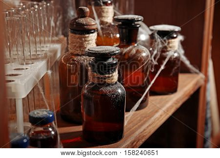 Vintage equipment of chemical laboratory on wooden shelf, closeup
