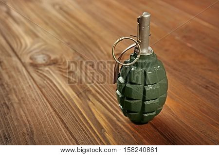 Close up view of hand grenade on wooden background
