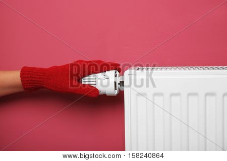 Female hand in warm glove on temperature regulator of heating battery on pink background, closeup