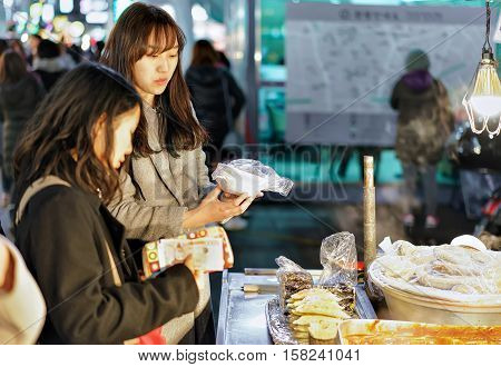Seoul South Korea - March 14 2016: Young girls buying street food at the stall at Myeongdong open street market in Seoul South Korea