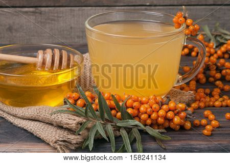 Tea of sea-buckthorn berries with honey on sackcloth and a wooden background.