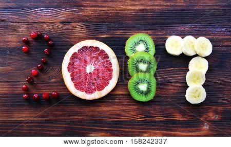 new year 2017 of fruit and berries on wooden background