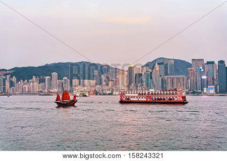 Junk Boat At Victoria Harbor Of Hong Kong At Sundown