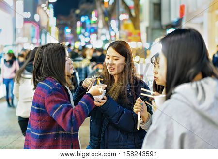 Korean Girls Tasting Street Food At Myeongdong Market In Seoul