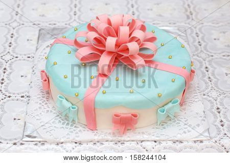 Homemade blue mastic cake decorated with pink ribbons, closeup