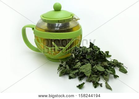 Green tea in the teapot, and dried lemon balm on a white background.
