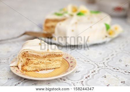 Piece of white mastic cake decorated with yellow flowers, closeup