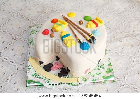 Creative mastic cake in palette form decorated with colorful paint and brushes, closeup