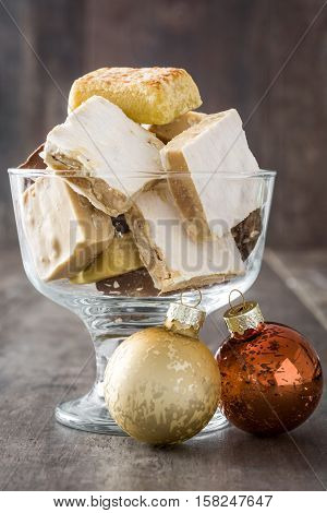 Variety of Christmas nougat in crystal glass and christmas ball on wooden background