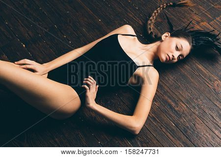 Young sexy mixed race caucasian woman vogue portrait with feather mohawk accessory wearing black bodysuit sitting on wooden floor on white wall background. Fashion concept.