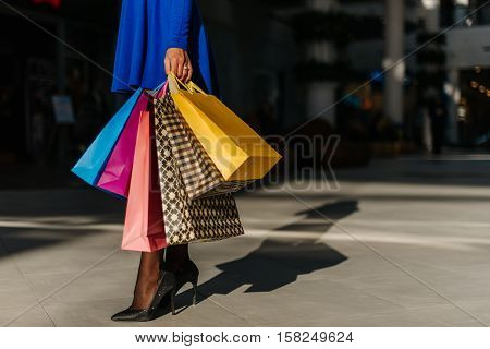 Beautiful legs of young pretty woman in short blue dress with long sleeves and shoes on hight heels after shopping in big mall. Many shopping bags in her hands.