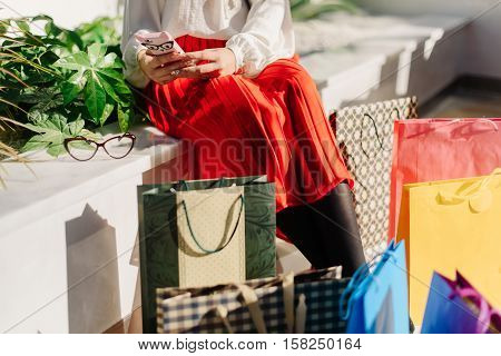 Beautiful young pretty woman in midi red skirt, white shirt and shoes on high heels after shopping in big mall sitting on the bench and chatting in internet using her phone with funny cat's face case. Glasses and many colorful shopping bags near.