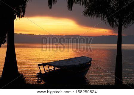 sun sets on the shores of lake Tanganyika and Congo border in the background, Kigoma, Tanzania