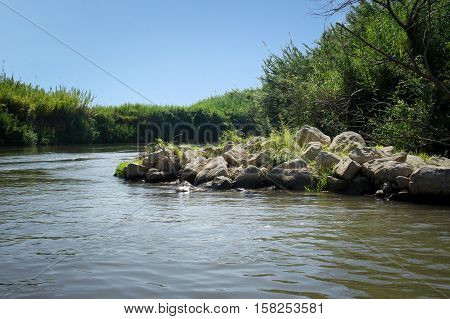 View of the slow river flow and the bushes growing along the banks of the Jordan River Israel