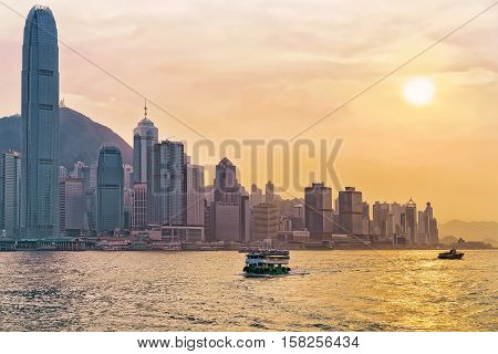 Star Ferry In Victoria Harbor And Hong Kong Skyline At Sundown