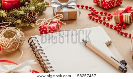 wish list among christmas presents on craft background