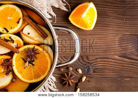 preparation of mulled wine in pot on wooden background top view