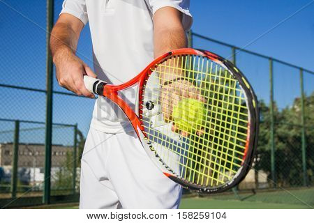 Close up photo of a racket and a tennis ball. Both are held by a professional tennis player with his hands while dispute a match against another player.