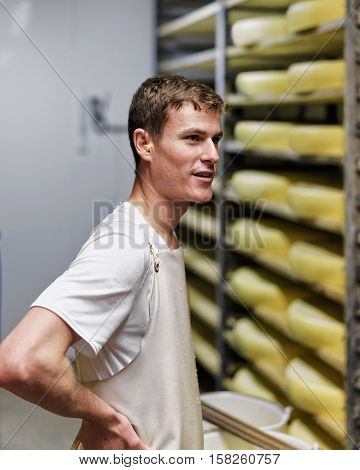 Worker At Storehouse Of Comte Cheese At Franche Comte Creamery