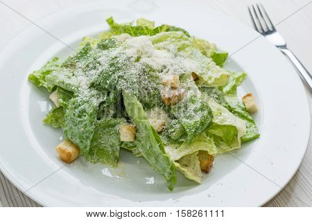 Caesar salad with cheese and croutons  on plate
