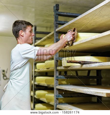 Worker Washing Wheel Of Comte Cheese At Franche Comte Creamery