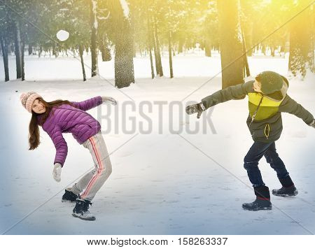 kids throw snowballs in the winter snowy park close up photo