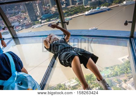 SHANGHAI CHINA - AUGUST 29 2016: An unidentified woman take selfie photo on transparent glass floor of TV Oriental Pearl Tower against Huangpu river and quay in Shanghai China on August 29 2016.