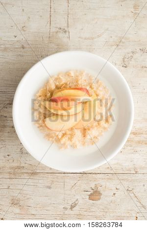 Bowl Of Porridge And Apple Slices On Wooden Background
