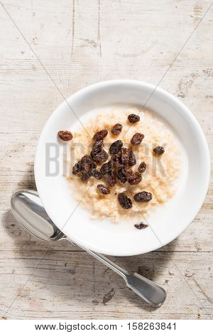 Bowl Of Porridge Oats And Raisins On White Wooden Background
