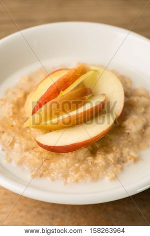 Bowl Of Porridge And Sliced Apples On Wooden Background