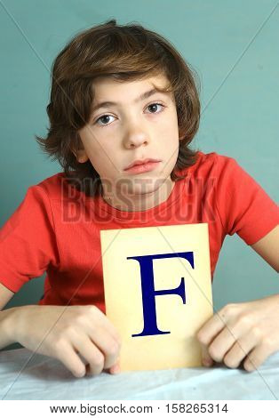 preteen boy with bad mark F - failure close up photo sad and frustrate