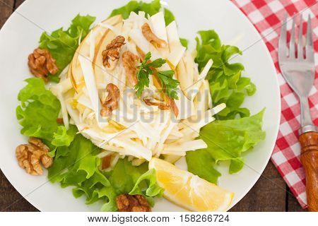 Waldorf Salad with green apples, celery and walnuts on a white dish, classic recipe, view from above