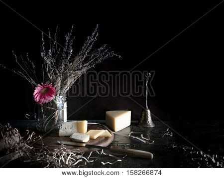 still life. Pink gerbera in a pot, cheese, Dor Blue, knife on a wooden table