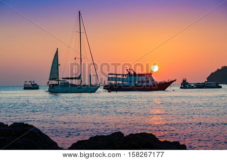 Colorful sunset with sailboat passenger boat and motor boat docking on the front at the golden hour and calm sea