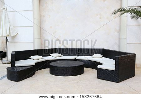 huge semicircular black sofa with white pillows and a table in hotel's interior
