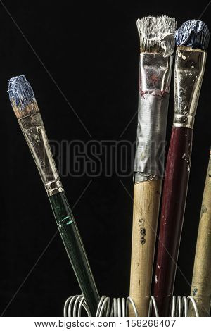 oil colors on paintbrushes studio macro closeuo black background poster