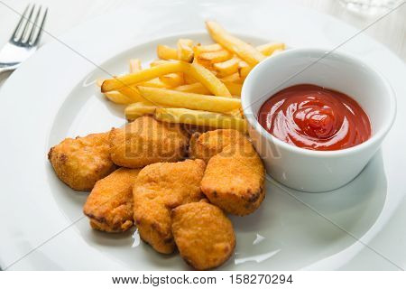 Chicken nuggets with french fries and ketchup
