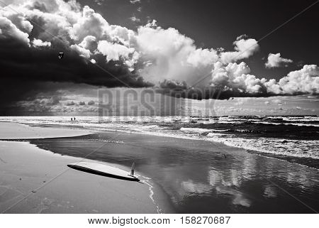 Majestic cloudscape, coastline before storm. Surfing board on the beach in front line. Black and white photography.