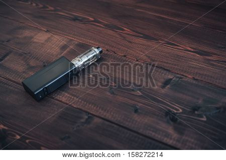 e-cig mod or electronic cigarette for vaping on a wooden table background