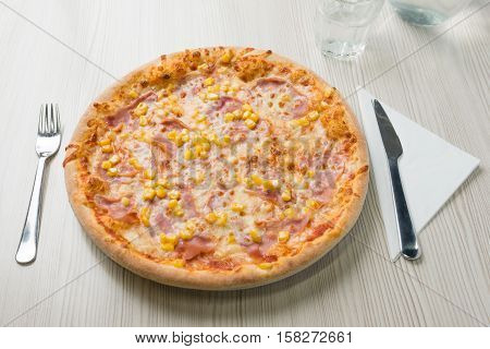 Pizza with ham and corn on the table