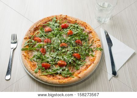 Delicious pizza with prosciutto tomato rucola and cheese on the table