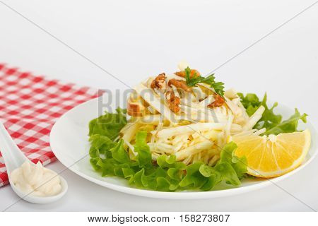 Waldorf Salad with green apples, celery and walnuts on a white plate